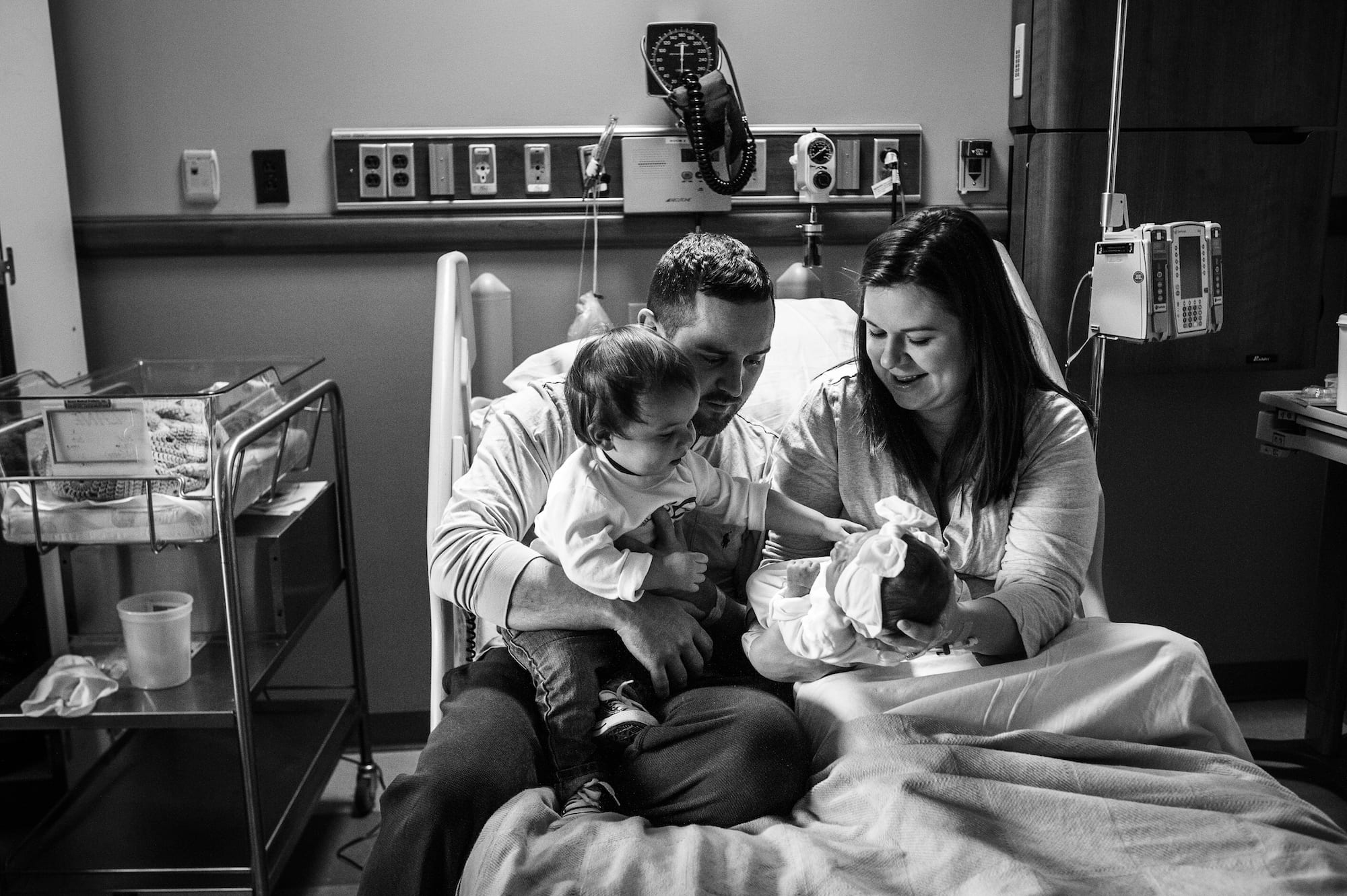 parents and sibling with newborn in hospital